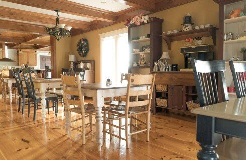 Dining area with hardwood floors and wood beamed ceiling and four tables and chairs