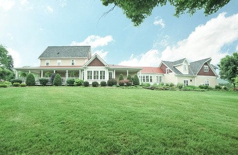 Large expansive home with wrap around porch surrounded by a beautiful lawn and landscaping