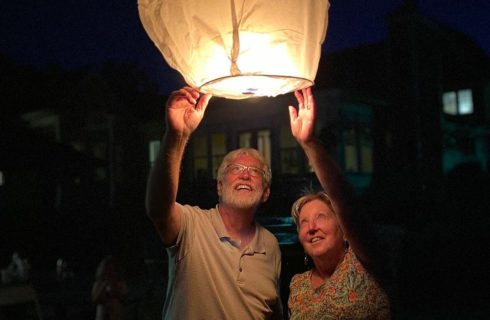 A man and woman reaching up to let go a large lit paper lantern into a night sky