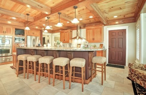 Beautiful kitchen with large island and stools, oak cabinets and stainless steel appliances