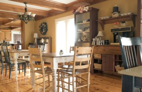 Dining area next to a kitchen with multiple tables with chairs and hutch area for coffee flanked with bookshelves
