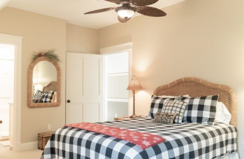 Queen bed with black and white buffalo check quilt and wicker headboard in a bright bedroom
