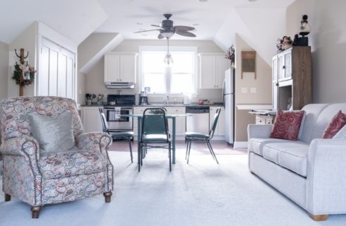 An open concept suite with small kitchenette, table with four chairs, couch and upholstered chair