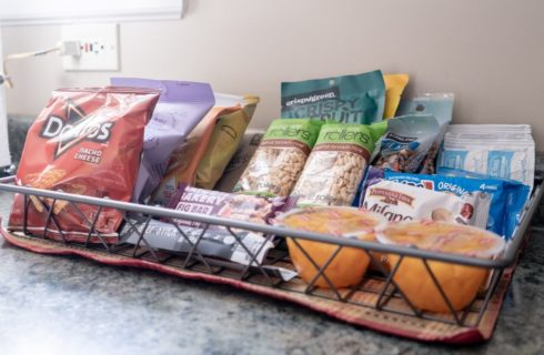 A wire basket on a counter filled with snacks including chips, cookies, fruit and nuts