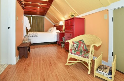 Spacious bedroom with hardwood floors, peach walls and white bed with red furniture