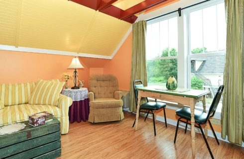 Bright rom with large window, hardwood floors, striped loveseat wth chest table and small table with two chairs