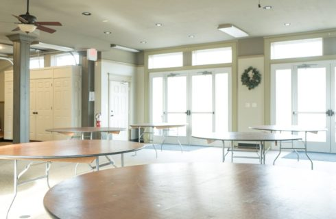 Bright and spacious event room with two sets of glass doors and round wood tables set up