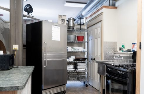 Kitchen area of an event space with large stainless steel refrigerator, stove, sink and wire rack full of supplies