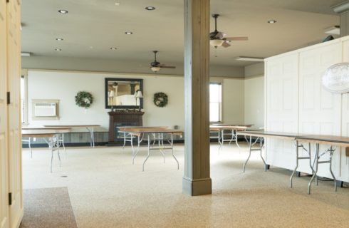Spacious event space with round and rectangular tables and two wreaths flanking a mirror over a decorative fireplace