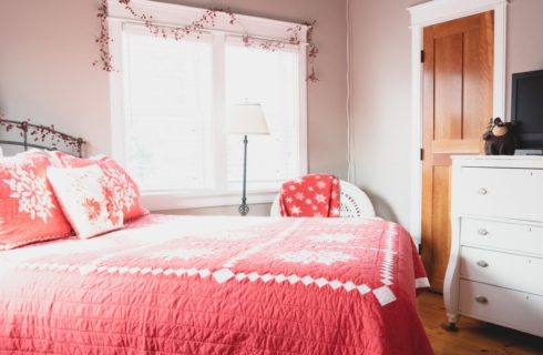 Farmhouse style bedroom with a combination of antiques and modern furniture, bright windows and dresser with TV