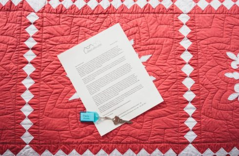 Typed letter with a set of keys sitting on top of a red and white quilt