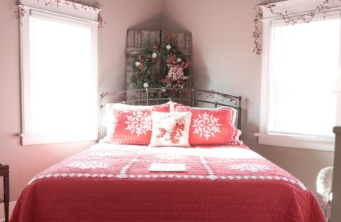 Farmhouse style bedroom with a combination of antiques and modern furniture and two bright windows