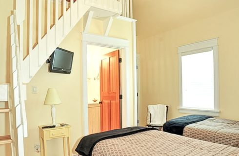 Two twin beds in a bedroom with stairs to a loft above and doorway into a bathroom
