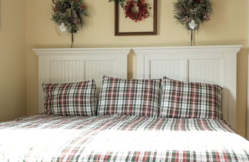 Two twin beds in a plaid quilt together as a king bed with light sconces and wreaths on the wall above