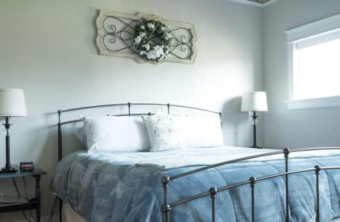 King bed with iron headboard and footboard with two side tables and lamps in a bright bedroom