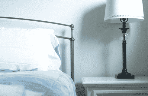 Bed with iron headboard with white side table holding a black lamp with a white shade