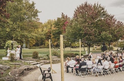 A bride and groom standing by a decorated arch while guests watch from an outdoor patio with string lights