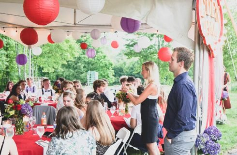 A large group of young people in formal attire gathered around tables under an outdoor tent