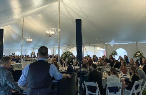 Wedding reception guests gathered under a large white tent with black chandelier lights and