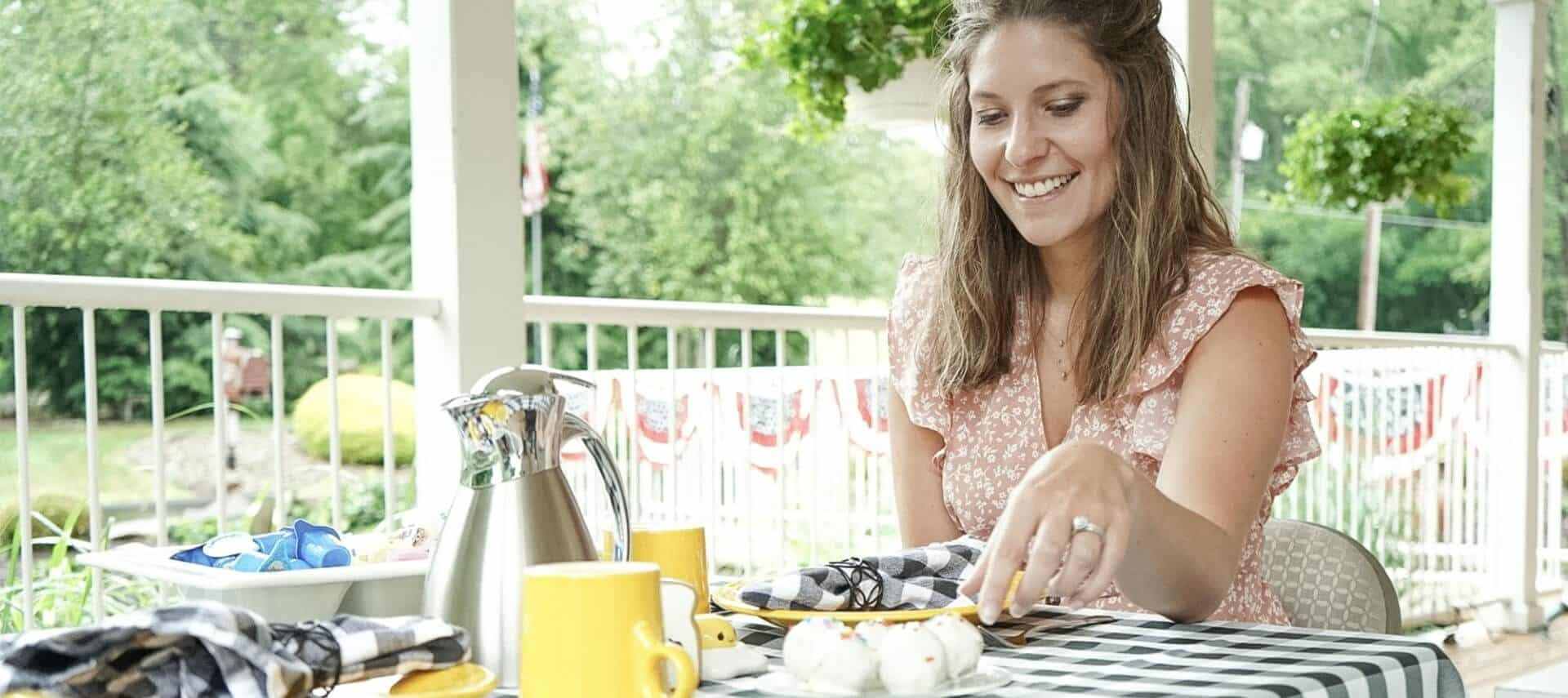 Woman smiling at a table for two on an outdoor patio next to a white railing with trees in the background