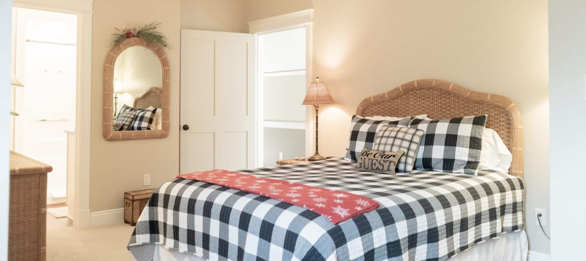 Bright bedroom with queen bed featuring a black and white buffalo check quilt and wicker headboard