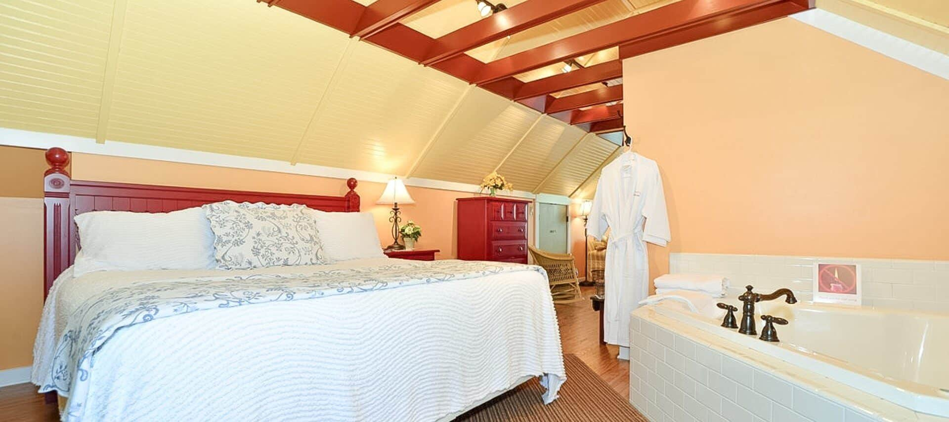 King sized bed with red headboard in loft bedroom with large jacuzzi tub, dresser and open wood beam ceiling