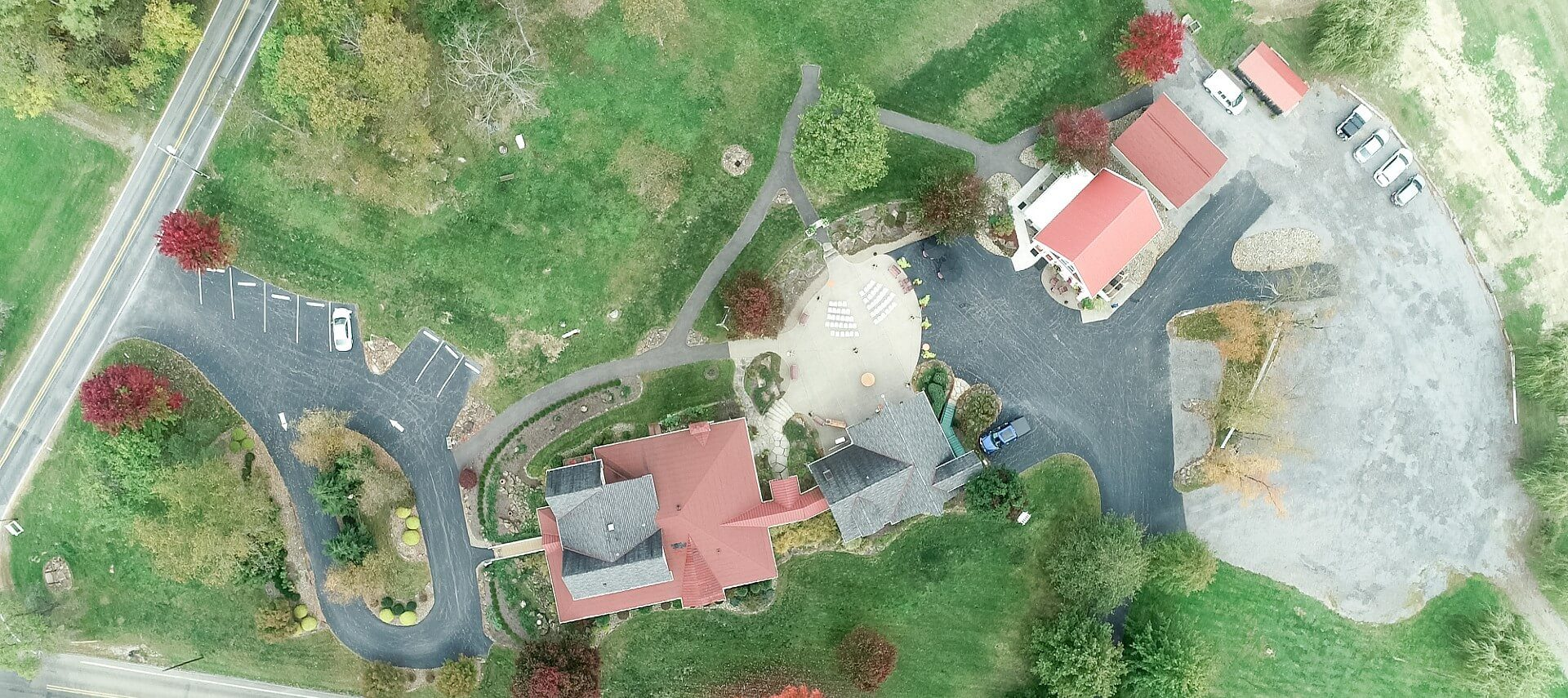 Aerial view of a home with multiple outbuildings, an expansive lawn and two parking lots