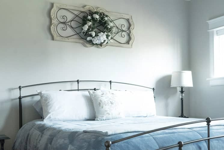 King bed with iron headboard and footboard, two side tables and lamps in a bedroom with a bright window