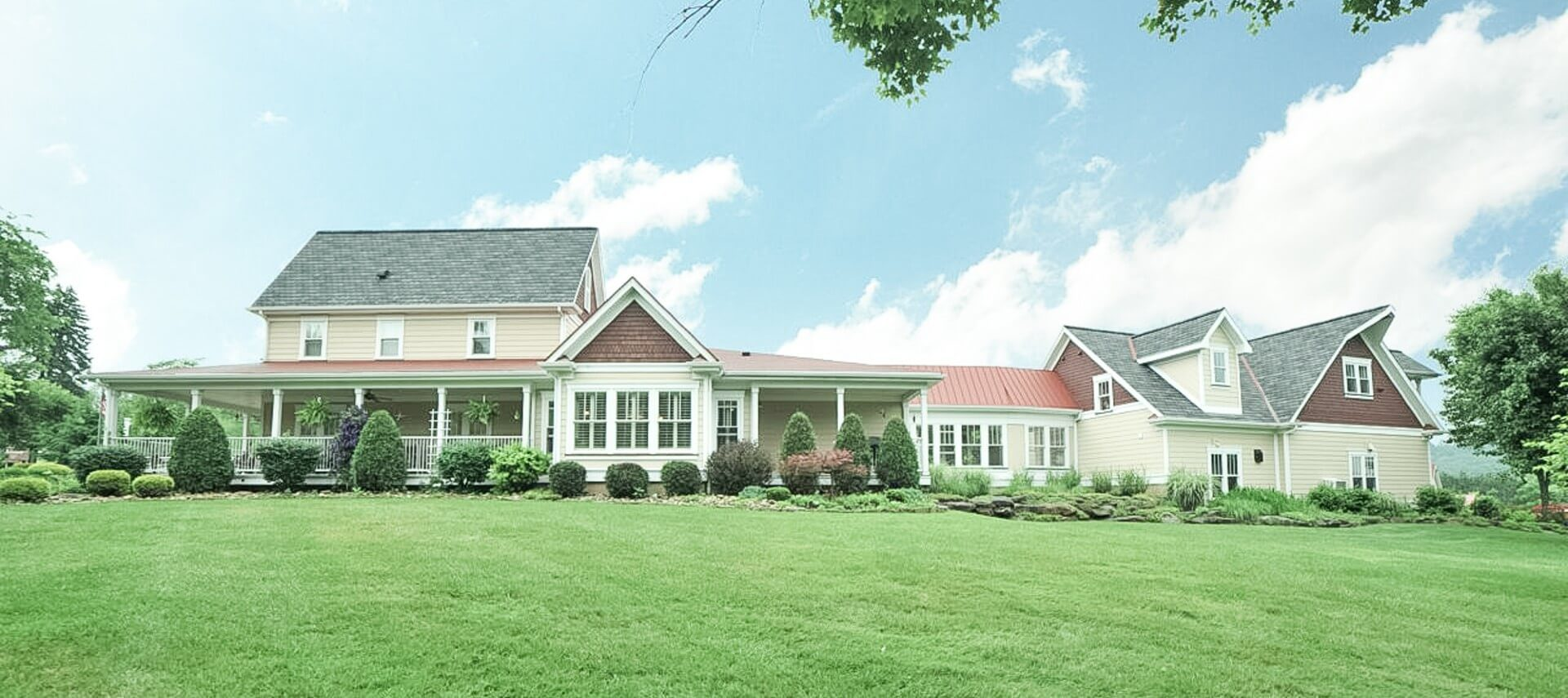 Expansive home wth yellow siding and large wrap around porch surrounded by lawn and landscaping