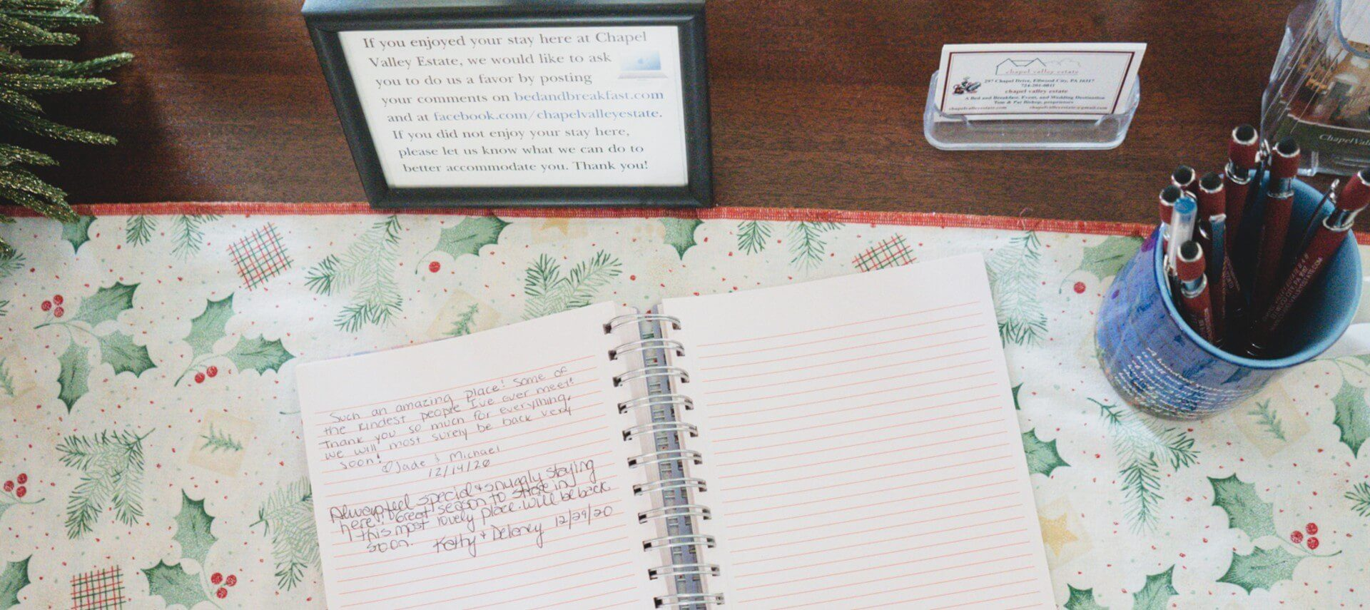 An open notebook with handwritten reviews on a Christmas themed placemat with cup of pens