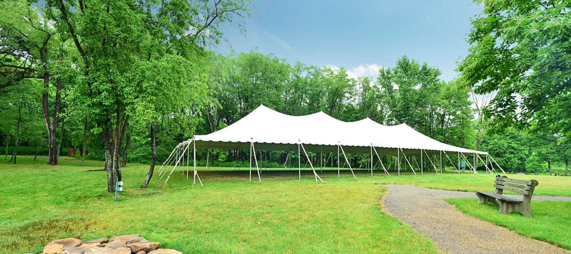 Large white outdoor event tent set up on a lawn surrounded by tall trees