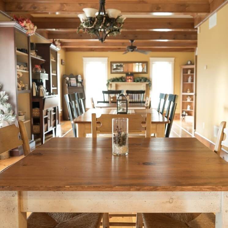 Dining room with four tables and chairs, wood beams on the ceiling and large bright windows